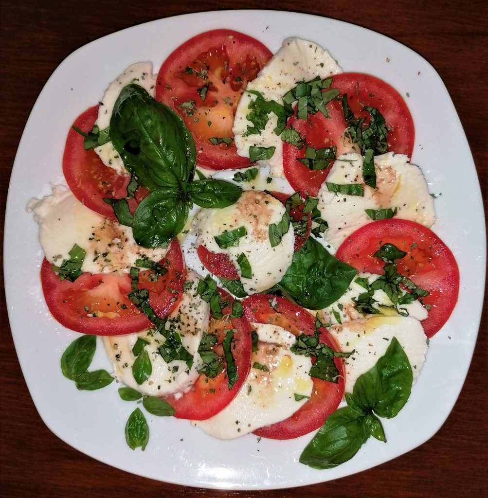 Plate of mozzarella and tomato slices sprinkled with fresh basil