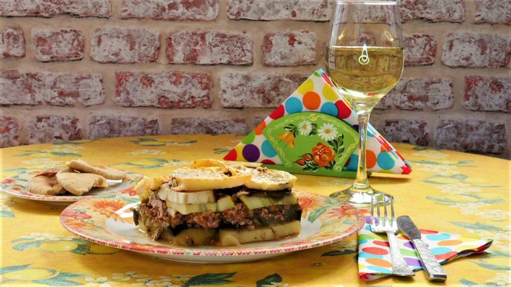 Greek moussaka dish and white wine