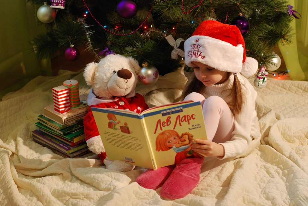 girl reading under Christmas tree